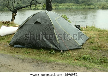 Tent on campsite by the river in rainy day - stock photo