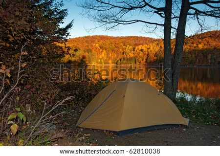 tent pitched next to an idyllic lake with blazing autumn colours, lac taylor, quebec