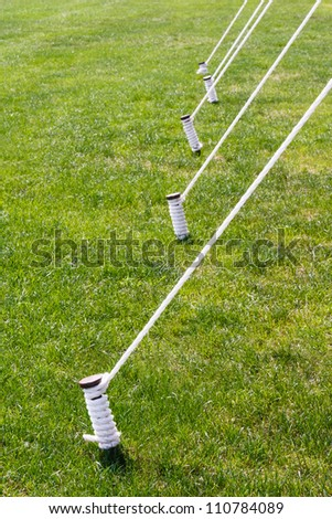 Tent stakes also known as tent pegs are wrapped and tied with white rope set against a vibrant green summer lawn - stock photo