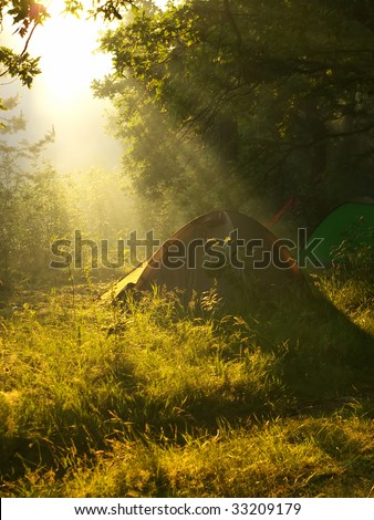 Tent under beams of the morning sun in the forest - stock photo