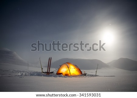 Tent under the Moon with amazing Halo - stock photo