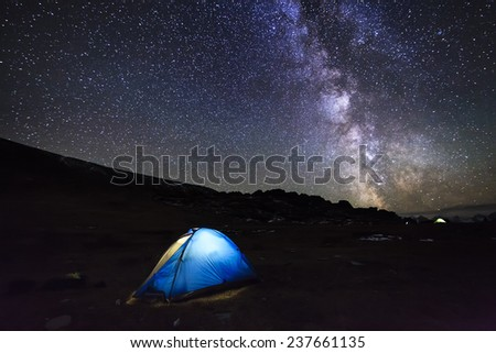 Tent with travelers in the mountains on the background of the magical starry sky. - stock photo