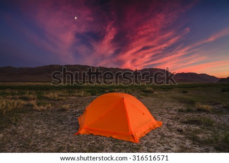 Tent with travelers on a background of mountains and clouds.