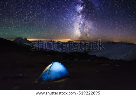 Tent with travelers under the amazing starry sky