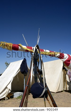 Tents and flag and armament on display at a civil war encampment. - stock photo