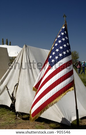 Tents and flag on display at a civil war encampment. - stock photo