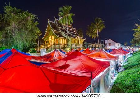 Tents of night market and Royal Palace in Luang Prabang, Laos - stock photo