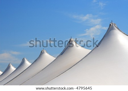 Tents on blue sky - stock photo