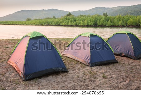 Tents on sea beach with green mangrove forest - stock photo