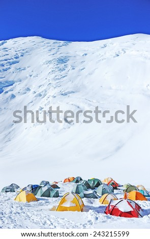 Tents on the glacier in high mountains - stock photo