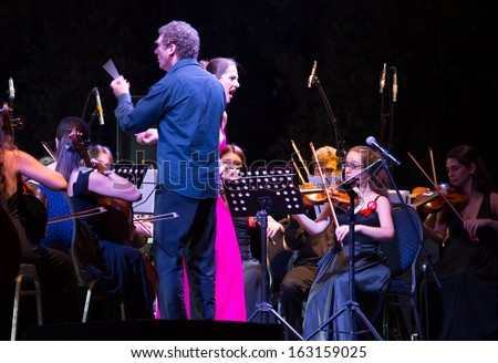 TEOS - IZMIR-JUNE 31: Turkish - Greek orchestra, Maestro Cem Mansur.the city of first actors union was (BC. 2000) the ancient city of Teos, on June 31 2013 in Teos izmir Turkey - stock photo