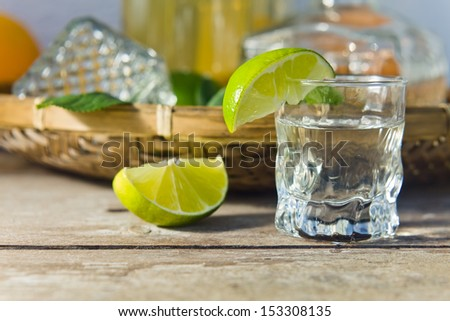 tequila and citrus fruits on a old table