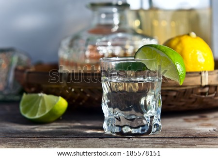tequila and citrus fruits on a old table - stock photo