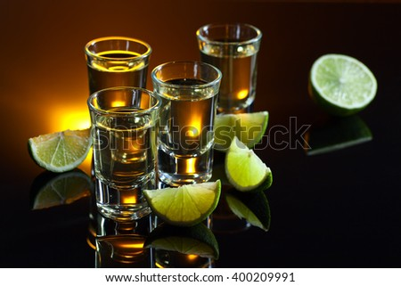 tequila and lime on a black glass table