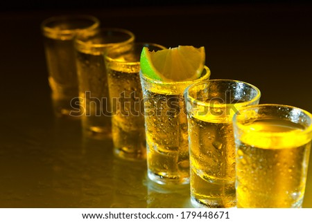 tequila and lime on a damp glass table
