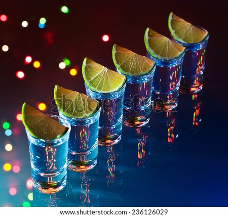 tequila and lime on a glass table - stock photo