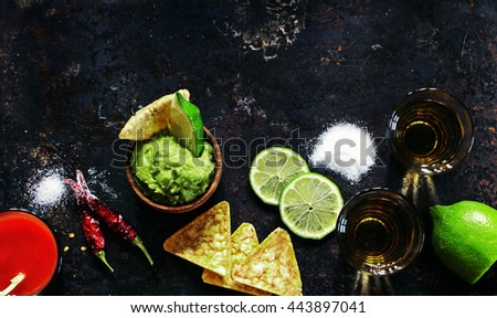 Tequila gold with sangrita chaser shots with lime slice with guacamole over old black metal surface, top view - stock photo