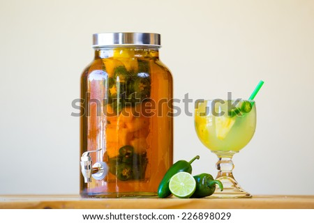 Tequila infused with jalapeno peppers in a tea jar at a restaurant bar. - stock photo