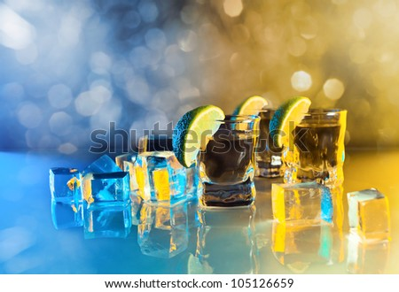 tequila , lime and ice on a glass table. - stock photo