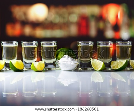 tequila , lime and salt on  table in bar - stock photo