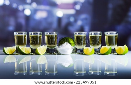 tequila , lime and salt on white reflexive table in bar - stock photo