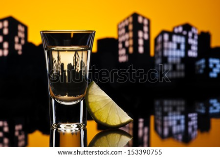 Tequila shoot in colorfull cityscape setting - stock photo