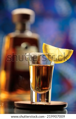 Tequila shot  and tequila bottle on bar background - stock photo