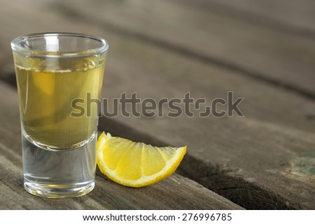 Tequila shot with lemon on the dark wood background with copy space - stock photo