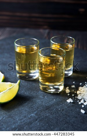 Tequila shot with lime and sea salt on black stone table