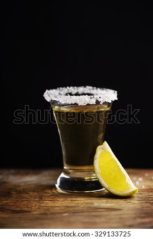 Tequila shot with salt on wooden table.