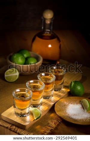 Tequila shots grouped together with a bottle and cut limes on a wooden surface