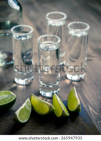 Tequila shots with lime wedges - stock photo