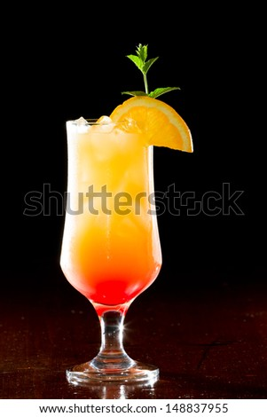 tequila sunrise, fresh orange juice with tequila and cherry juice served in a stem glass on a dark bar