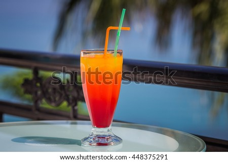 Tequila sunrise. Holiday cocktail on the terrace with a sea view. - stock photo