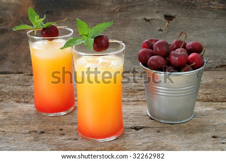 Tequila Sunrise/ Juice drink with fresh cherries and mint leaves shot on a rustic looking background. - stock photo