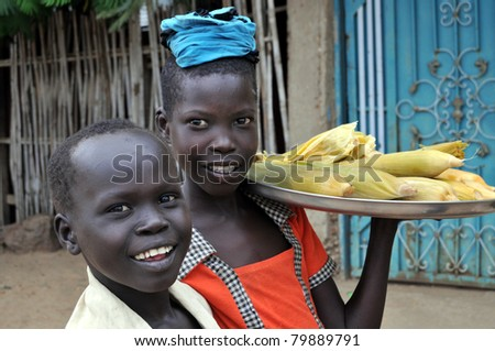 TEREKEKA - JUNE 11: Unidentified children selling cooked corn in Terekeka, South Sudan, on June 11, 2011. World Day Against Child Labour, launched by ILO, was observed on June 12, 2011. - stock photo
