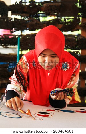TERENGGANU, MALAYSIA - APRIL16,2014 - An artist carefully trace on a traditional batik at Noor Arfa Craft Complex, Terengganu, Malaysia - stock photo