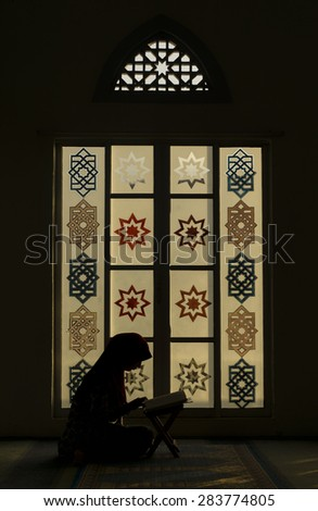 TERENGGANU, MALAYSIA-MAY 2015: Muslim woman reading Koran alone in the evening at Mukhtafi Bilal Shah Mosque on MAY, 2015 in Mukthafi Bilal Shah Town, Terengganu. - stock photo