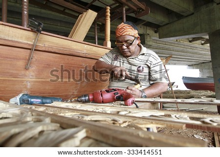 Terengganu , Malaysia - 30 October 2015 : A craftsman carpenter artist craftsmanship do sculpture in wooden ship factory for Ministry of Tourism Malaysia.