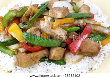 Teriyaki Chicken stir-fry on a bed of rice with colorful peppers and onions - stock photo