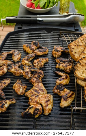 Teriyaki chicken wings with garlic bread and herbs - stock photo