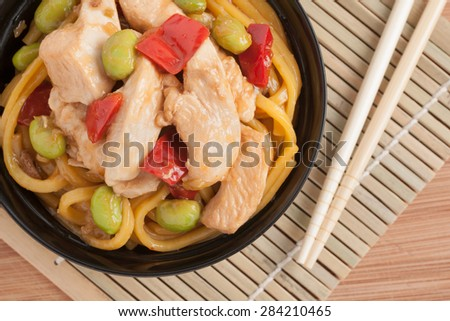 Teriyaki chicken with egg noodles edamame and red peppers top down view - stock photo