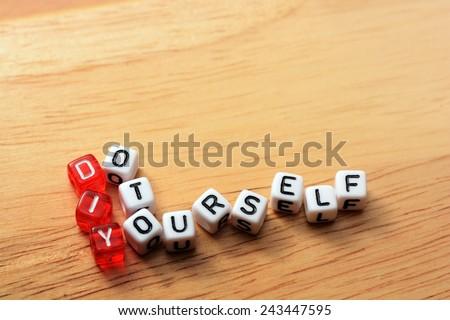 Term DIY spelled from toy cubes, dice letters on wooden background - stock photo