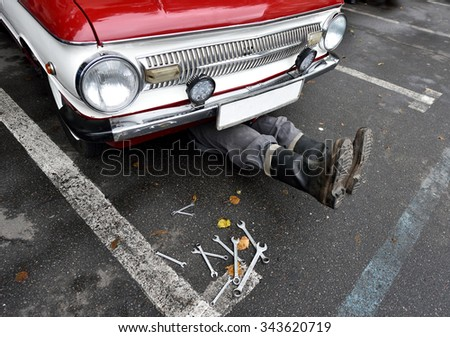 Ternopil, Ukraine September 27, 2015: The feet of the master, which can be seen under the car and keys for repair on the exhibition of vintage cars in Ternopil. - stock photo