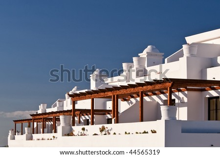 Terrace houses with balconies over a blue sky. - stock photo