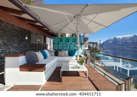 Terrace lounge with comfortable divans and lake view in a luxury house - stock photo