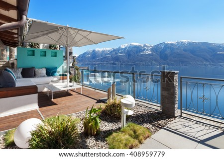 Terrace lounge with lake view in a luxury house - stock photo
