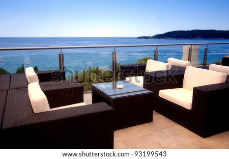 Terrace lounge with rattan armchairs and sea view in a luxury resort . - stock photo