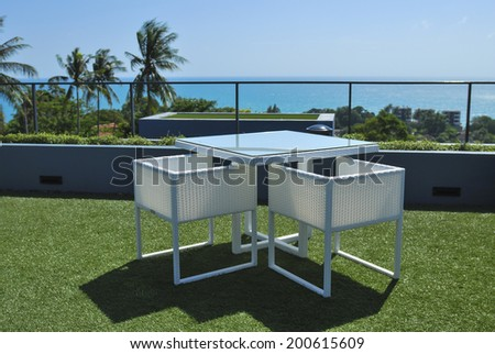 Terrace lounge with white rattan armchairs and sea view in a luxury resort . - stock photo