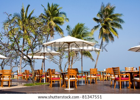 Terrace of a restaurant with white sun shades on a beautiful beach - stock photo